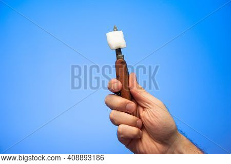 Single White Marshmallow On A Small Pocket Knife Blade Held In Hand By Caucasian Male Hand Isolated