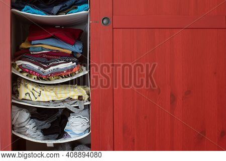 Variety Of Used Folded Clothing Inside Home Closet Red Wooden Cupboard.