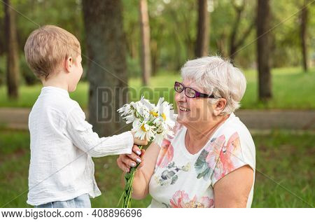 Beautiful Boy Giving A Flower To Grandma. Happy Mothers Day. Grandson And Grandmother Spending Time