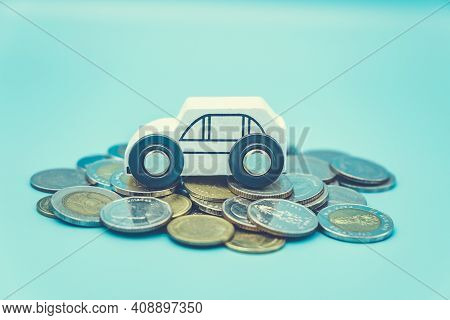 White Toy Car On Pile Money Stack Coins Growth On Blue Background. Miniature Automobile Model And Bu
