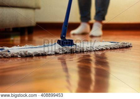 A Woman Cleaning The Hardwood Floor, With A Close-up Of The Mop And A Blurred Background Of Feet And