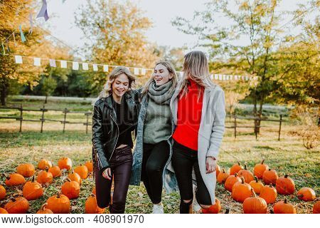 Three Teenage Girls Dance And Laugh Among A Mountain Of Pumpkins At The Fall Fair, N The Background