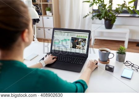 technology, post production and vlog concept - close up of woman working in video editor program on laptop computer working at home office
