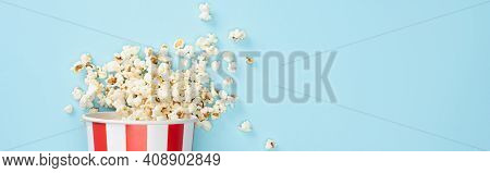 Top View Of Paper Bucket With Crunchy Popcorn On Blue, Banner, Cinema Concept.
