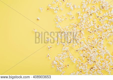 Top View Of Crunchy Popcorn Scattered On Yellow, Cinema Concept.
