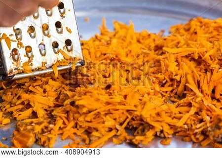 Using Grater Or Shredder To Cut Turmeric Roots Into Fine Pieces For Medicinal And Food Purposes.