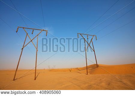 Electrical power lines on pylons stretch in sandy Namib desert, Namibia, Africa