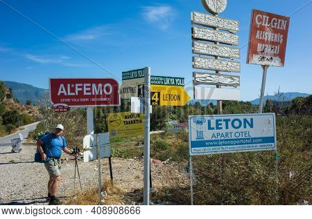 Kumluova, Turkey - 10 October, 2019: Signs on Lycian way hiking trail, Man tourist standing next to many different shape sign boards, directions indicators, arrows, advertising signs