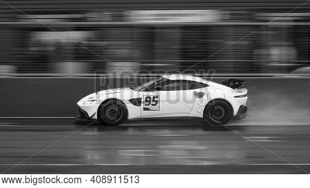 A Panning Shot Of A Racing Car As It Circuits A Track.
