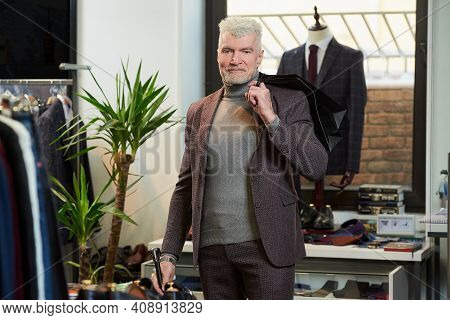 A Happy Mature Man With Gray Hair And A Sporty Physique Threw Two Black Paper Bags Behind His Back W