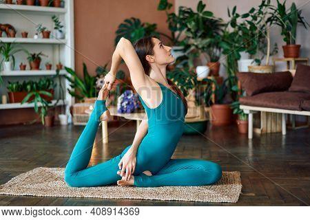 Young Woman Practicing Yoga Doing One Legged King Pigeon Pose At Home. Eka Pada Rajakapotasana Asana