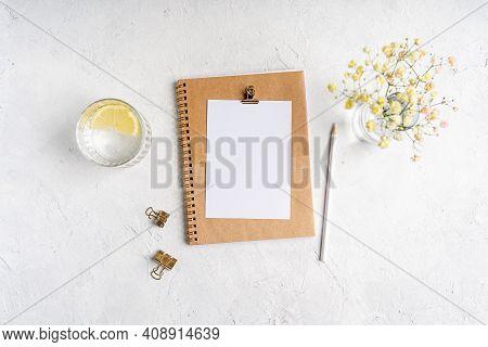 Top View Blank Paper Notebook, Flowers, Golden Paper Binder Clips, Water With Lemon And Pen. Desktop