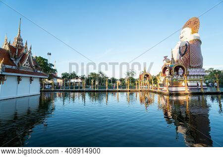 Koh Samui, Thailand - January 10, 2020: Woman In A Red Dress Standing On A Bridge To A Giant Colorfu