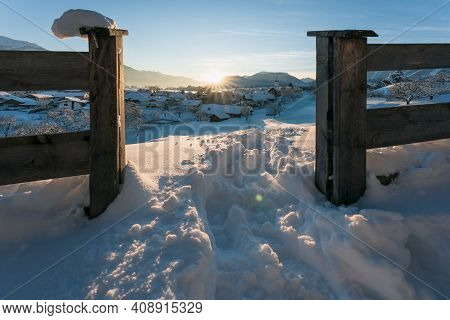 Snow Covered Rural Winter Landscape Seen Through Fence During Sunset With Sun Star Between Alpine Mo
