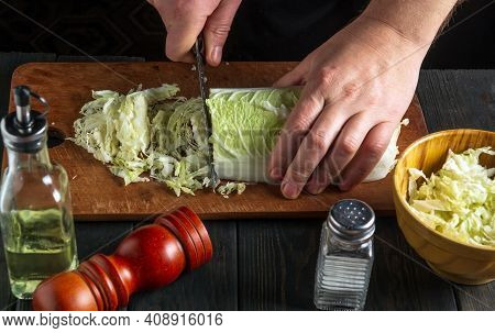 The Chef Prepares A Salad Of Napa Cabbage. Close Up Of Chef Is Hand Cutting Cabbage With A Knife On
