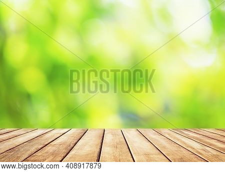 Wooden Table Top On Blur Abstract Green Background. Spring Green Abstract Background With Bokeh Ligh