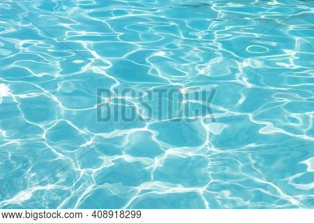 Shining Blue Water Ripple Background. Surface Of Water In Swimming Pool.