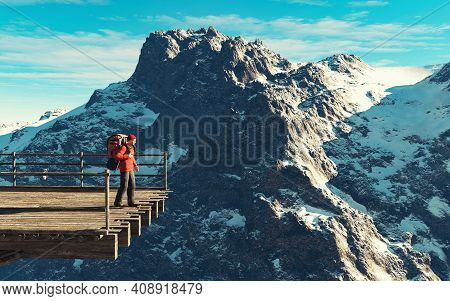 Hiker With Backpack Standing On A Bridge In Front Of A Mountain During Winter . This Is A 3d Render