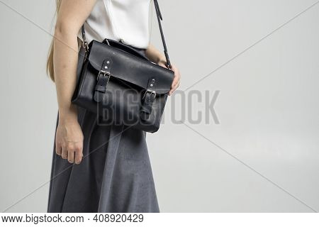 Small Black Leather Bag Over A Woman Shoulder On A White Background. Shoulder Handbag. Woman In A Wh