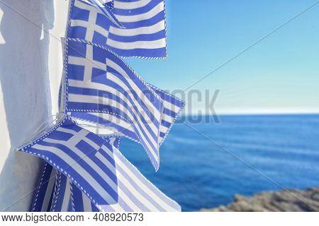 Greek Flags Hanging On A Wall Near The Mediterranean Ocean In Greece