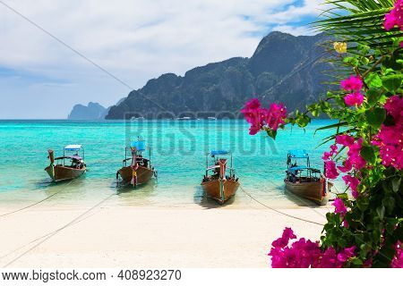 Thai Traditional Wooden Longtail Boats And Beautiful Sand Beach With Pink Flowers At Koh Phi Phi Isl