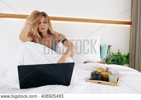 Sensual Beautiful Young Woman Watching Show Episode Or Presentation On Laptop Screen When Having Bre