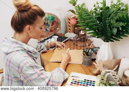 Creative Young Woman In Plaid Shirt Sitting At Her Desk At Home And Writing In Planner Or Gratitude