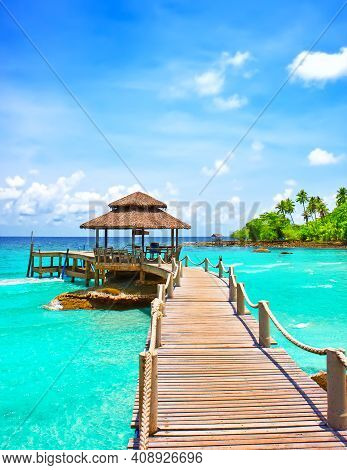 Sea with pier under blue cloudy sky in Koh Kood, Thailand.