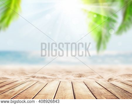 Wooden Table Top On Blue Sea And White Sand Beach Background. Coconut Palm Trees Against Blue Sky An