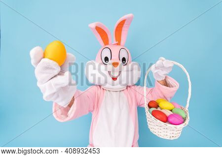 Easter Bunny Or Rabbit Or Hare Holds Egg With Basket Of Colored Eggs, Having Fun, Celebrates Happy E