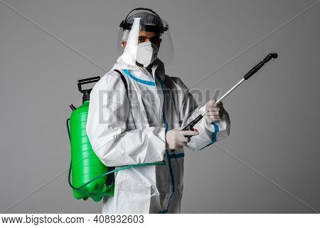 Full Length Profile Shot Of A Medic Man In A Hazmat Suit Santizing With A Spray Isolated On White Ba