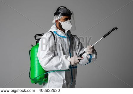 Man In Protective Suit And Face Protection Mask Spraying Interior Using Chemical Agents To Stop Spre