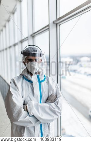 Male Doctor In A Protective Suit And A Medical Mask Sits Near A Window In A Hospital.