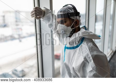 Man In Hazmat Protective Suits Look Glass At Home Or Office During Outbreak Of Coronavirus, Covid-19