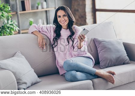 Full Length Photo Of Happy Nice Charming Young Woman Sit Sofa Hold Phone Free Time Rest Indoors Insi