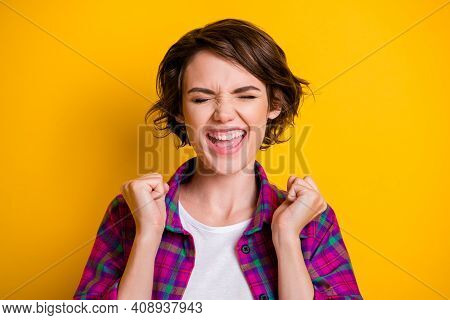 Photo Of Lucky Overjoyed Woman Hold Fists Closed Eyes Anticipate Wish Isolated On Yellow Color Backg