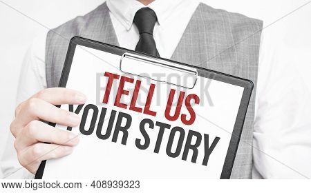Tell Us Your Story Inscription On A Notebook In The Hands Of A Businessman On A Gray Background, A M