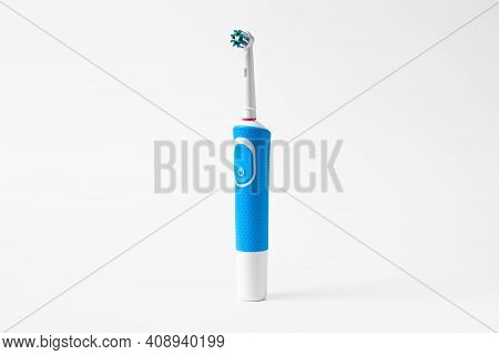 Modern Electric Toothbrush Standing On A White Background. Controlled Tool For Daily Oral Care.