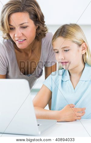 Mother and daughter using the laptop in the kitchen