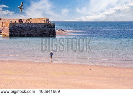 25 July 2018: Marazion, Cornwall, Uk-tourists Walk Along The Beaches Of Marazion, An Ancient Market