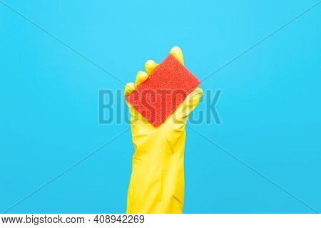 Housewife's Hand In Yellow Rubber Glove Holding Red Washing Sponge, Blue Background. Household Clean