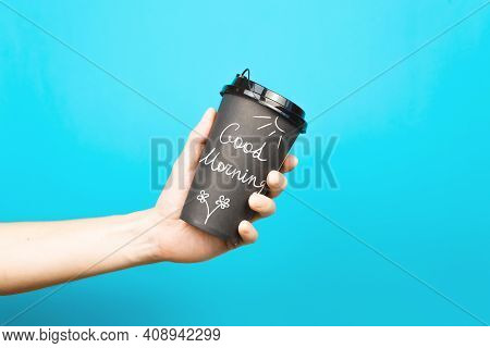 Male Hand Holding Cardboard Cup Of Coffee With Hand Lettering Good Morning, Blue Background Indoors.
