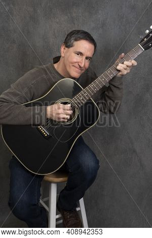 Man Sitting On Stool Playing Acoustic Steel Stringed Guitar