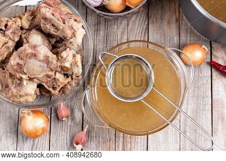 Passing The Bone Broth Through A Sieve. Concentrated Bone Broth In A Bowl