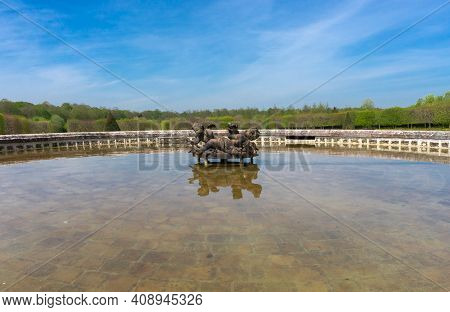 Versailles, France - May, 2019. Green Water And Bronze Figures Of Cupids From An Inoperative Fountai