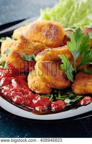 Fried Chicken Nuggets With Ketchup, Sprinkled With Chopped Parsley On A Black Plate.
