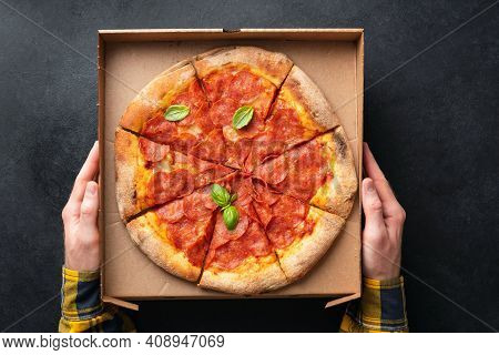 Pepperoni Pizza In Carton Cardboard In Male Hands, Black Background. Top View. Pizza Delivery Servic