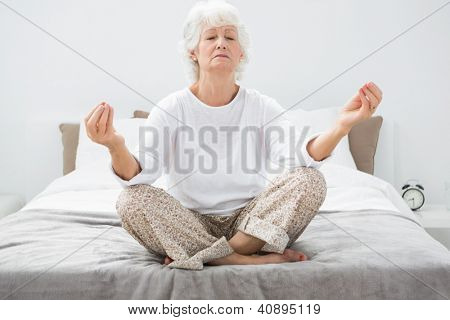 Old woman relaxing on the bed