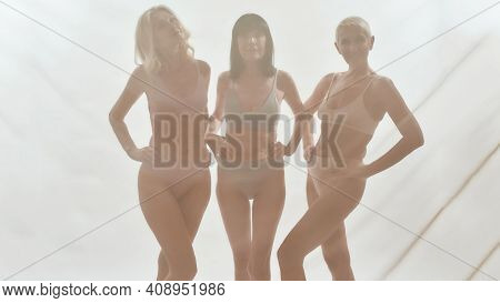 Lovely Ladies Placing Hands On Their Hips And Looking Straight While Standing After A Studio Sheer C
