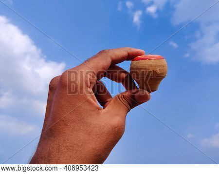 South Indian Man Hand Holding Wooden Spinning Top. Cloud Background
